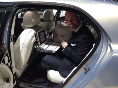 Brandon demonstrates the seat-back laptops and leather cushions featured in the $300,000 Bentley Mulsanne.